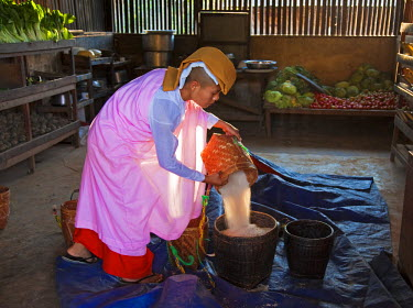 Myanmar, Burma, Loikaw. A young female nun at an orphanage, measuring out rice in the storeroom. Loikaw.