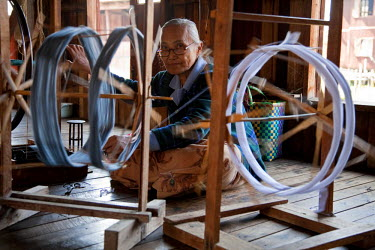 MYA1500 Myanmar, Burma, Inle Lake.  Spinning silk in a weaving factory, Inle Lake.