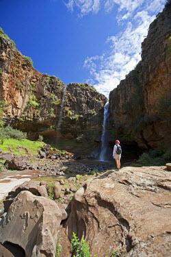 LES1163 Lesotho, Malealea. A tourist looks at a waterfall whilst on a trek from Malealea. MR