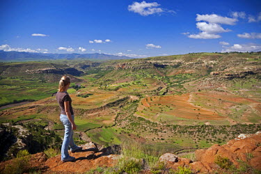 LES1174 Lesotho, Malealea. A tourist stands at the edge of a cliff and looks over the stunning scenery around the town of Malealea. MR