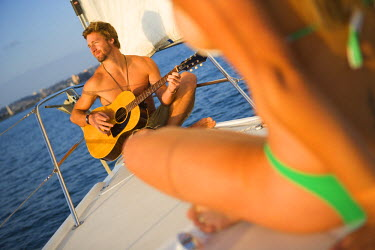 AR9768900026 A man plays guitar for a woman in a bikini while sitting on the bow of a sailing yacht in San Diego Harbor, California.