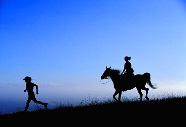 AR9774700006 Silhouette of a person running with another person riding a horse behind.