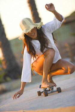 AR9585300003 Woman skate boards at beach.