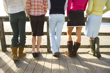 AR9575000012 Women's legs wearing boots and shoes.