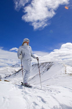 AR3082800139 Woman enjoying the view of the Continental Divide in a white ski suit in Colorado.