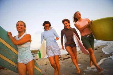 AR9907200017 Four women walking down the beach in Newport Beach, California carrying their surfboards at sunset.