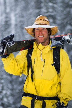 AR3325100067 A man smiles wearing a snowy cowboy hat and carrying his skis .