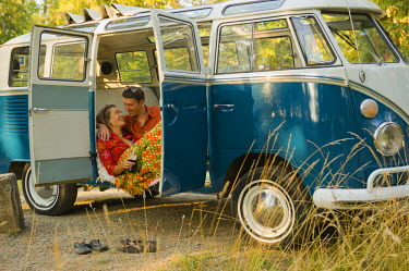 AR3510600007 A young couple relax inside a classic van.
