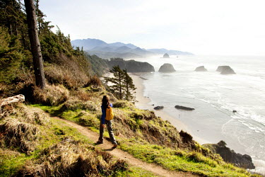 AR3912500014 A woman hiking a secluded path along the coastline. Ecola State Park, Oregon, USA