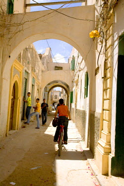 LIB1452 Tripoli, Libya; A youth riding a bicycle in the streets of the old Medina of Tripoli