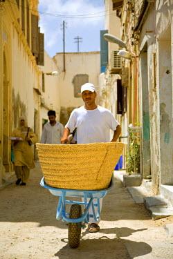 LIB1453 Tripoli, Libya; A man carrying a wheelbarrow through the steets of the old Medina