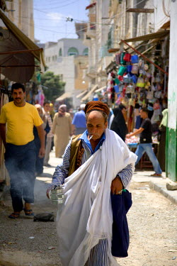 LIB1454 Tripoli, Libya; A Libyan man in traditional clothes smoking a cigarette and carrying incense through the 'souk' of the old Medina