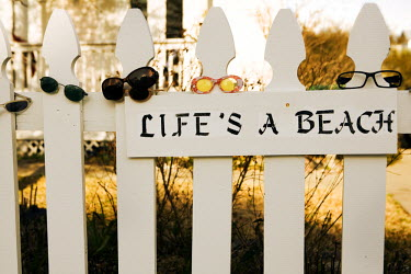 AR3923700011 A picket fence is covered with sunglasses and has a sign that reads life's a beach.