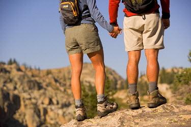 AR8593600018 Couple hold hands and gaze over the horizon. Aspen, Colorado. USA
