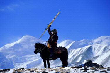 AR0620901502 Tibetan yak herders carry skis to base of Ani Maqin mountain, China