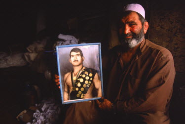 AR9071900034 An Afghan man holds a portait of himself as an Olympic wrestler in one of the old bazaars of Kabul. Afghanistan