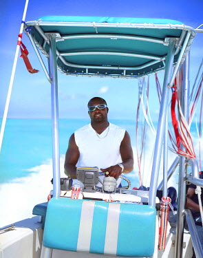 AR9105700014 A parasailing boat operator drives tourists out to sea. Off Grace Bay Beach, Providenciales, Turks and Caicos, British West Indies.
