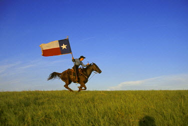 AR9180500008 A young cowgirl carries a Texas flag while in a full gallop on horseback, Texas. USA