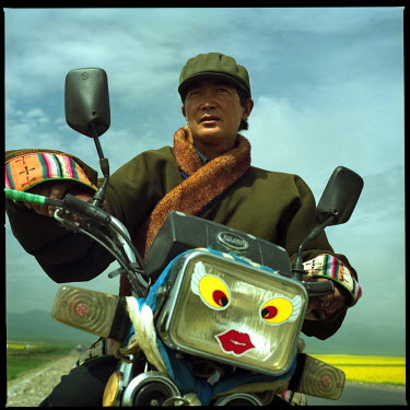 A Tibetan man with his motorcycle along a highway in the Qinghai Province, central China.