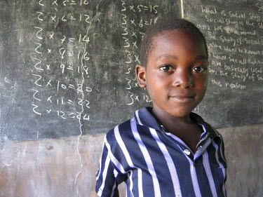 AR9569100040 Young boy in a classroom learning his mathematic timetables on the blackboard in a school in the coastal village town of Sussex,  Freetown Pennisula, Sierra Leone