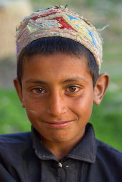 AR9677500043 A young boy smiles shyly  in the Tajik village of Dera Jawal, at the base of the Band-e Baba range,  Herat Province, Afghanistan
