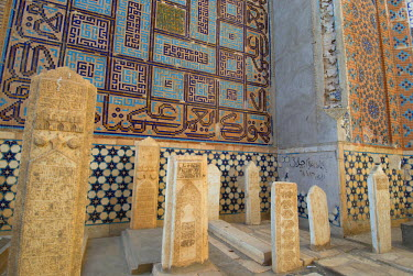 AR9677600032 Elaborately carved headstones of graves stand before walls covered with ancient mosaics at the Sufi shrine of Khwaja Abdulla Ansari, at Gazargah, outside of Herat, Afghanistan.