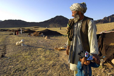 AR9677600039 A Pashtun man and his young son stand outside their low tent at a camp in the dry hills below the desert mountain range of Dau Shakh, Gurian district in  Herat Province, Afghanistan.