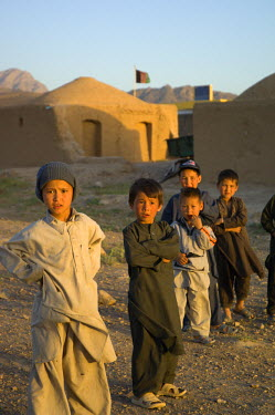 AR9677600041 Pashtun boys stand outside their mud homes in a village near the desert mountain range of Dau Shakh, Gurian District in Herat Province, Afghanistan