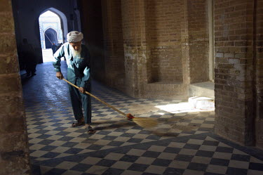 AR9677600044 An elderly man sweeps a corridor in the Friday Mosque or Masjid-i Jami, the largest mosque in Herat, dating to the 1200's, Herat, Afghanistan