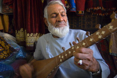 AR9677600047 A shopkeeper in a store near the Friday Mosque  plays Tanboor, a classical stringed instrument of Central Asia, in Herat, Afghanistan