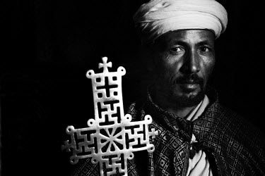 AR9787600013 Priest with golden cross inside one of the buried churches from Lalibela Town, Lalibela, Ethiopia.