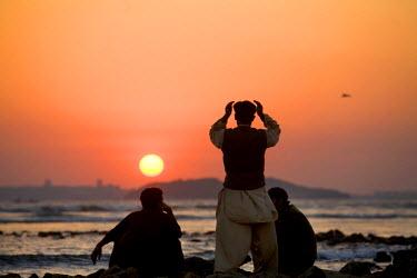AR9789700007 Men watch the sunset and pray at Clifton Beach in Karachi, Pakistan