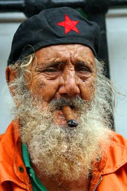 AR9795800002 A man with a cigar poses for a portrait near the Plazas de Armas in Havana, Cuba.