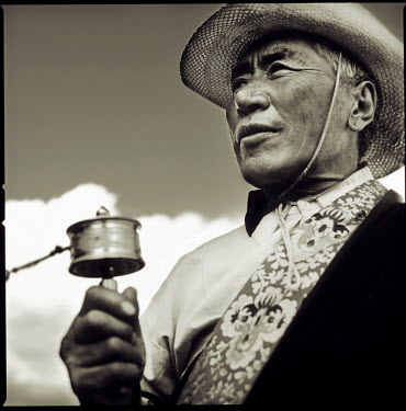 AR9813000002 A Tibetan pilgrim spins a prayer wheel on his journey to Lhasa, Nac Chu, Tibet Autonomous Region, China.