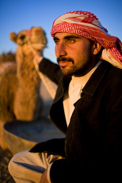 AR9844900048 Portrait of a young Syrian Bedouin man with his camel in the desert, Palmyra, Syria