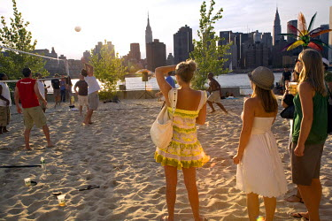AR9851900019 Playing and watching beach volleyball on an urban fake beach with a perfect view of the Midtown Manhattan skyline at Water Taxi Beach, Long Island City, Queens, New York