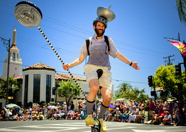 AR9891100002 A man on his unicycle joins characters and dancers in the annual Santa Barbara Solstice Parade, California