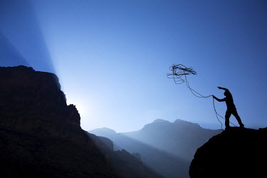 AR9938700030 A man tosses a rope in preparation to start a climb in the Grand Canyon in Arizona.