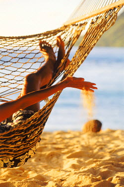 NP00865577 A woman playing with sand and lying in the hammock, Huahine Island, Tahiti, French Polynesia