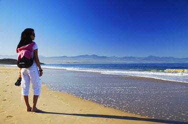 SAF6476AW Woman standing on beach, Plettenberg Bay, Western Cape, South Africa (MR)
