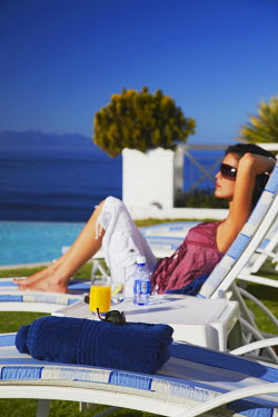 SAF6459AW Woman relaxing poolside at Plettenberg Bay Hotel, Plettenberg Bay, Western Cape, South Africa (MR)