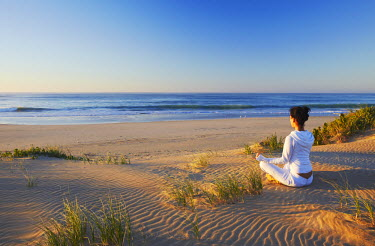 SAF6450AW Woman practicing yoga on beach at dawn, Jeffrey's Bay, Eastern Cape, South Africa (MR)
