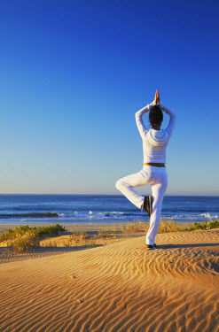 SAF6452AW Woman practicing yoga on beach at dawn, Jeffrey's Bay, Eastern Cape, South Africa (MR)
