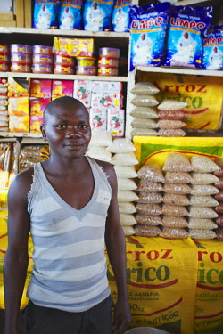 MOZ1528AW Vendor standing in front of stall in municipal market, Maputo, Mozambique