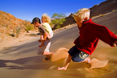 NAM6015 Namibia, Damarland, Brandberg.  Young children running down a sand dune near Brandberg, Namibias highest mountain. (MR)