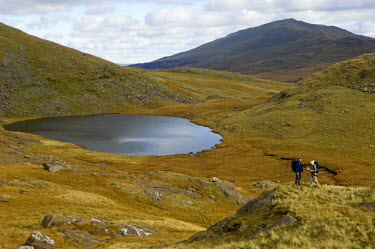 WAL7104 UK, North Wales, Snowdonia.  Man and woman trekking on the flanks of Mt Snowdon.  (MR)