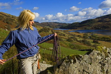 WAL7107 UK, North Wales, Snowdonia. Girl with rope and climbing harness preparing to go rock climbing.  (MR)