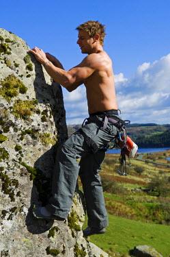 WAL7111 UK, North Wales, Snowdonia.  A man rock climbing on a large granite boulder near Snowdon.  (MR)