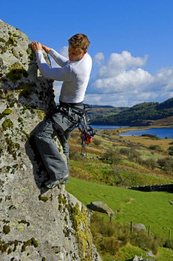 WAL7112 UK, North Wales, Snowdonia.  A man rock climbing on a large granite boulder near Snowdon.  (MR)