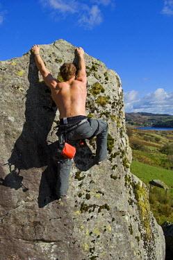 WAL7113 UK, North Wales, Snowdonia.  A man rock climbing on a large granite boulder near Snowdon.  (MR)